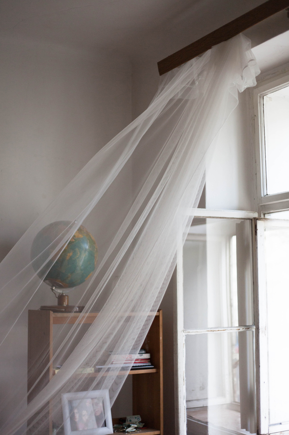 Curtains blowing in an open window with a globe on a shelf