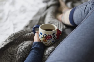 A woman drinking coffee while still in her pajamas in bed