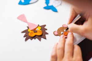 Cutting and pasting felt animals to a scrap book