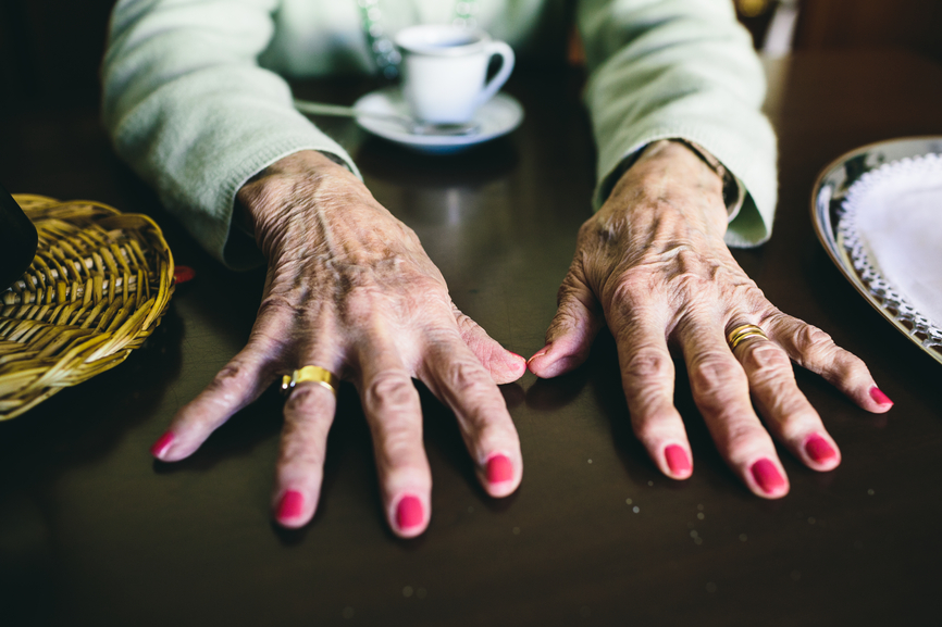 Old hands spread on a table with pink nail polish and a ring.