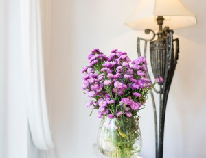 Purple flowers in glass vase for decoration in front of white wa